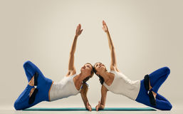 Yoga in pair. women. Duo. Balance on floor Royalty Free Stock Images