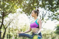 Yoga in the park healthy exercise. woman do lotus yoga pose stock images