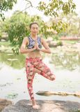 Yoga in the park healthy exercise. woman do lotus yoga pose. stock photo