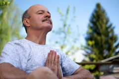 Yoga at park. Senior man with mustache with namaste sitting.Concept of calm and meditation. Royalty Free Stock Images
