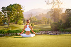 Yoga at park. With view of the mountains, with sunlight. Young woman in lotus pose sitting on green grass. Concept of calm and meditation Royalty Free Stock Images