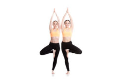 Yoga with partner, Tree pose. Two beautiful sporty girls in orange sportswear practice yoga with partner, exercise for spine, standing symmetrical in asana Stock Images