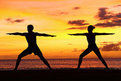 Yoga people training and meditating warrior pose. Yoga people training and meditating in warrior pose outside by beach at sunrise or sunset. Woman and men yoga Royalty Free Stock Images