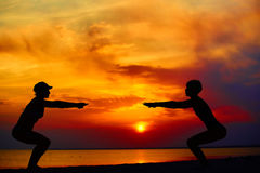 Yoga people training and meditating in warrior pose outside by beach at sunrise or sunset. Woman and men yoga exercising training in serene ocean landscape Royalty Free Stock Image
