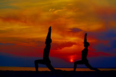 Yoga people training and meditating in warrior pose outside by beach at sunrise or sunset. Woman and men yoga exercising training in serene ocean landscape Stock Photography