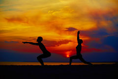 Yoga people training and meditating in warrior pose outside by beach at sunrise or sunset. Woman and men yoga exercising training in serene ocean landscape Stock Image