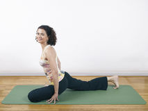 Yoga Pigeon Pose. A woman holding a yoga pose on a floor mat Stock Photography