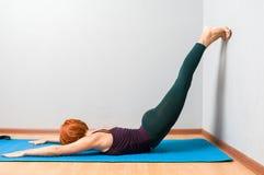 Yoga posant sur un fond gris de studio Image libre de droits