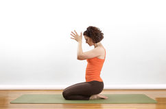 Yoga pose. Women showing  a Anjili Mudra yoga pose on a green mat Royalty Free Stock Photo