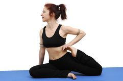 Yoga pose. Woman in yoga posture sitting on a blue rug, isolated with clipping path Royalty Free Stock Image