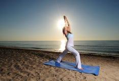 Yoga pose on beach. Woman doing yoga pose on beach with sunburst Stock Photo