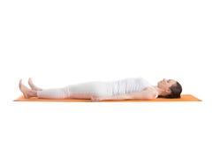 Yoga pose Savasana. Sporty beautiful young woman in white sportswear lying with closed eyes on orange mat in Shavasana (Savasana, Corpse Pose), studio shot Stock Image