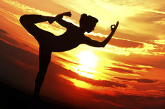 Yoga pose at sunset 4. Woman doing a yoga pose at sunset Royalty Free Stock Photography