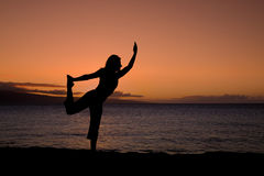 Yoga Pose in the Sunset. A woman practicing yoga silhouetted in the sunset on the beach Stock Photo