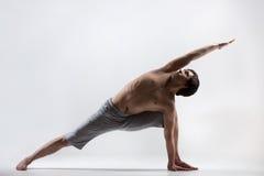 Yoga Pose uthitta parshvakonasana. Sporty muscular young man working out, yoga, pilates, fitness training doing lunge exercise, Utthita Parsva Konasana (Extended stock photography