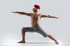 Yoga Pose Warrior 2 in Santa Claus hat Stock Photography