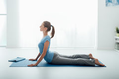 Yoga pose. Woman practicing yoga and meditation at home on the floor, she is doing the cobra pose Royalty Free Stock Photos