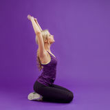 Yoga pose. Young sporty women on a purple background. Exhales, pulls hands up Stock Photos