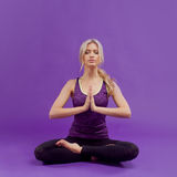 Yoga pose. Young sporty women on a purple background Stock Photo