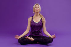 Yoga pose. Young sporty women on a purple background royalty free stock image