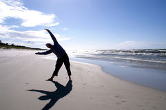 Yoga in position. Woman exercises yoga on beach in radii of sun stock photography