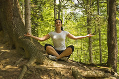 Yoga position in nature. Young woman doing yoga in nature and sitting in lotus position near a tree in forest,breathing the clean air of mountains,more photos Stock Images
