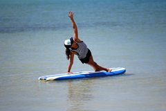 Yoga position on surfboard. Woman in side plank yoga position on surfboard in ocean (Vasisthasana Royalty Free Stock Photo