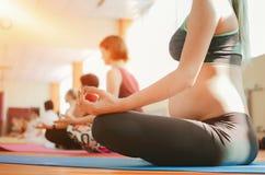 Yoga pour les femmes enceintes Jeune belle fille enceinte dans les vêtements de sport faisant le yoga dans le gymnase photos stock
