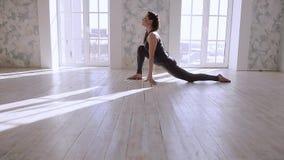 Yoga practicante Adolescente hermoso en la posición de la yoga del entrenamiento de la ropa de los deportes en club de salud almacen de video