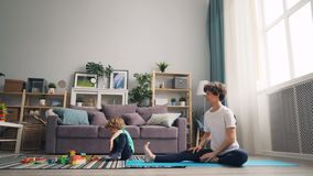 Yoga practicante de amor de la mamá que mira a su hijo el jugar con los ladrillos y hablar almacen de video