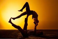 Yoga practicante de dos personas en la luz de la puesta del sol Foto de archivo libre de regalías
