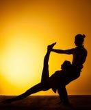 Yoga practicante de dos personas en la luz de la puesta del sol Imagenes de archivo