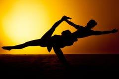 Yoga practicante de dos personas en la luz de la puesta del sol Fotos de archivo