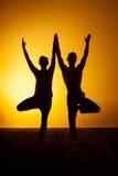 Yoga practicante de dos personas en la luz de la puesta del sol Imágenes de archivo libres de regalías