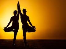 Yoga practicante de dos personas en la luz de la puesta del sol Fotos de archivo libres de regalías