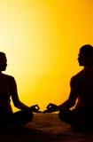 Yoga practicante de dos personas en la luz de la puesta del sol Fotografía de archivo