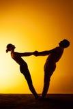 Yoga practicante de dos personas en la luz de la puesta del sol Foto de archivo