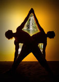 Yoga practicante de dos personas en la luz de la puesta del sol Imagen de archivo libre de regalías