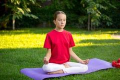 Yoga practicante de la muchacha adolescente en hierba en el parque Fotografía de archivo libre de regalías