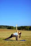 Yoga practicante de la muchacha en campo Imágenes de archivo libres de regalías