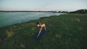 Yoga practicante de la muchacha hermosa en parque de la mañana Mujer triguena que hace yoga almacen de metraje de vídeo