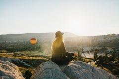 Yoga practicante de la muchacha hermosa joven en la cima de una montaña en Cappadocia en la salida del sol Prácticas de la relaja Imagenes de archivo