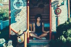 Yoga practicante de la muchacha rizada joven mezclada en pagoda Imágenes de archivo libres de regalías