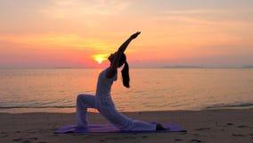 Yoga practicante de la mujer asiática en el mar de la puesta del sol almacen de metraje de vídeo
