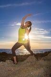 Yoga practicante de la mujer asiática sana en el top del amarillo de la playa que lleva Foto de archivo