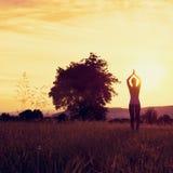 Yoga practicante de la mujer atlética joven en un prado en la puesta del sol Imagenes de archivo