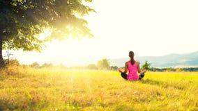 Yoga practicante de la mujer atlética joven en un prado en la puesta del sol Imagen de archivo