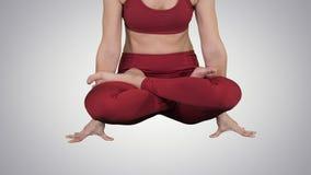 Yoga practicante de la mujer atractiva deportiva, colocándose en ejercicio de la escala, actitud de Tolasana en fondo de la pendi metrajes