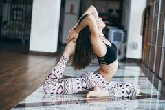 Yoga practicante de la mujer atractiva joven cerca de la ventana Foto de archivo libre de regalías