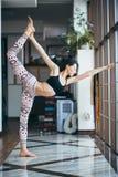 Yoga practicante de la mujer atractiva joven cerca de la ventana Imagen de archivo libre de regalías